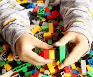 child-s-hand-building-plastic-toy-blocks_38607-79