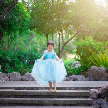 portrait-cute-smiling-little-girl-princess-costume-walking-down-stairs-park_53945-774